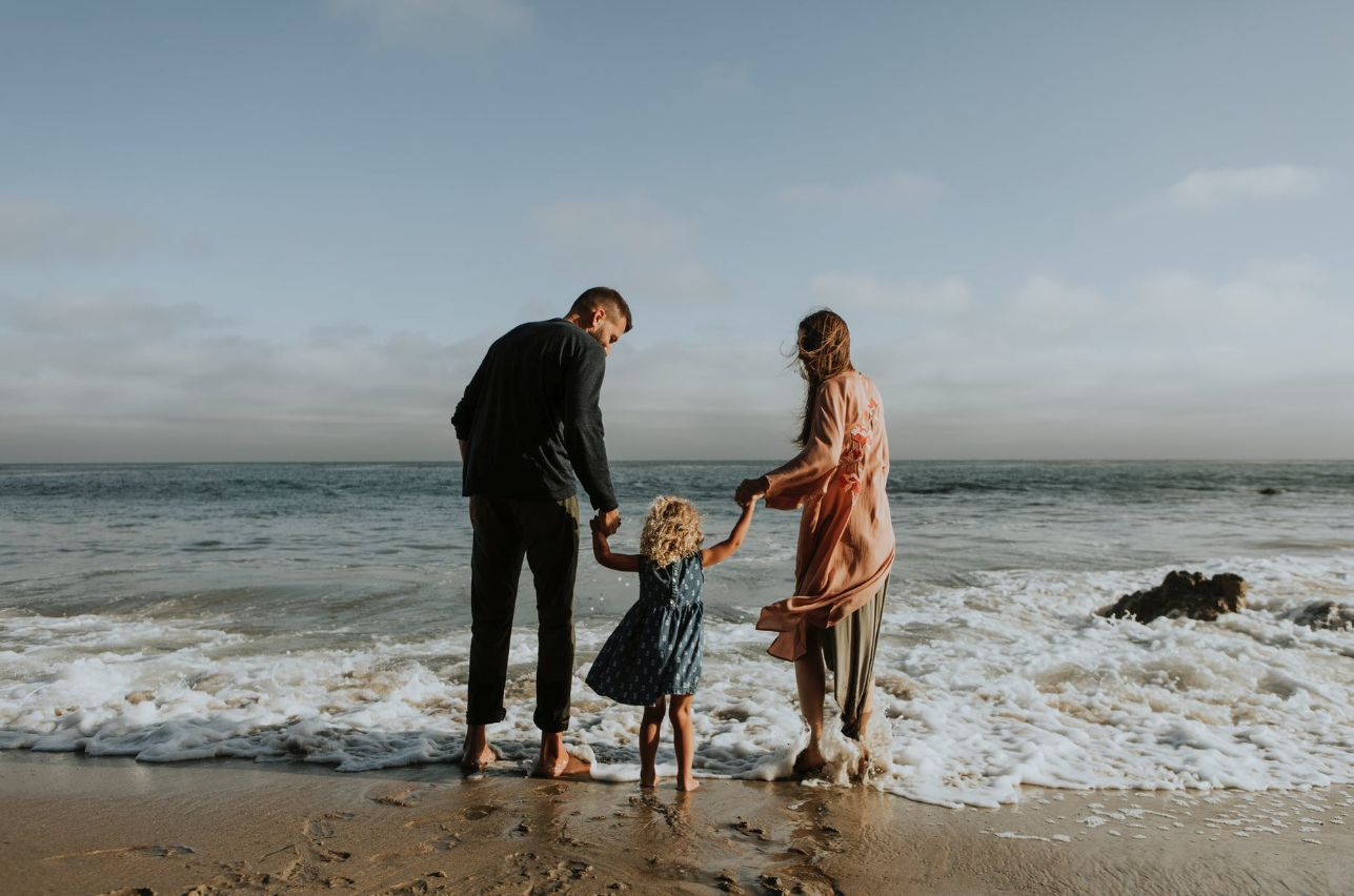 parents and child on a beach